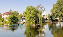 Kanus auf der Gänsehavel in Fürstenberg - Wohnhäuser und Bäume in der Sonne am Flussufer.