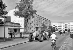 Wohnblocks und Traktor vor einem Imbiss - Kießener Ring / Hagenow, Schwarz-Weiss.