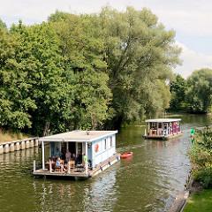 Hausboote in Fahrt auf den Schleusenkanal der Stadt Rathenow - Bäume am Ufer des Kanals.