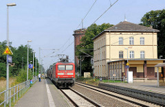 Haltestelle Hagenow Land - ein Zug fährt am Bahnsteig ein. Im Hintergrund das alte Postgebäude und der Wasserturm.