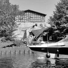 Ruine der Steinhavelmühle an der Steinhavel in Fürstenberg ( Havel) - Bug eines fahrenden Sportboots.