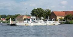 Die Autofähre überquert bei Pritzerbe die Havel - am Ufer Wohnhäuser des Dorfes.