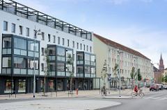 Wohnhäuser mit verglasten Balkons - Geschäfte in der Berliner Strasse von Rathenow; im Hintergrund der Kirchturm der Sankt-Marien-Andreas-Kirche.