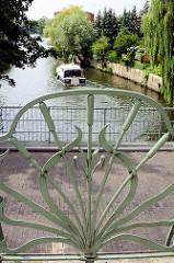 Jugendstilgeländer / Eisendekor auf der Rathower Brücke über den Stadtkanal - ein Motorboot fährt Richtung Havel.