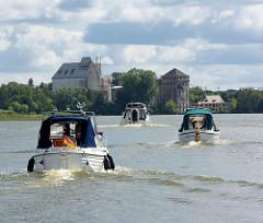Motorboote überqueren den Röblinsee und folgen dem Lauf der Havel in Fürstenberg; im Hintergrund Industriegebäude einer verlassenen Fabrik am Seeufer.