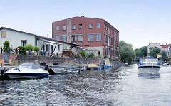 Stadtkanal von Rathenow - Sportboote liegen am Ufer; ein Motorboot fährt Richtung Schleuse / Stadthafen; einfache Industriearchitektur, Gewerbegebäude / Ziegelbau.