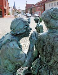 Fiek'n Brunnen vor dem Rathaus von Hagenow, Rathausplatz / Lange Strasse. Der Brunnen 2007 errichtet, Künstler Bernd Streiter - ein Schusterjunge belauscht zwei Frauen beim Tratschen.