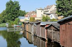 Bootshäuser aus Holz am Ufer der Gänsehavel in Fürstenberg - im Hintergrund Wohnhäuser an der Havelstrasse.