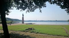 Mahn- und Gedenkstätte Ravensbrück am Seeufer des Schwedtsees - Skulptur die Tragende; auf der anderen Seite des Sees der Kirchturm der Stadtkirchen von Fürstenberg / Havel.