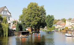 Kanus in der Gänsehavel von Fürstenberg; Wohnhäuser und Bootshäuser am Ufer des Nebenarms der Havel.