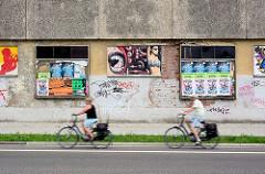 Hausfassade mit Plakaten und Wandmalerei - Radfahrer; Fotos aus Rathenow, Landkreis Havelland.