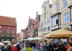 Historische Häuser, Aussengastronomie unter Sonnenschirmen auf der Strasse am Lüneburger Stintmarkt.