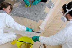 Laminierungsarbeiten beim Bau des Daysailors Lütje 35 in Hamburg - überstehende Glasfasermatte wird mit einer Schere beschnitten.