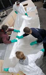 Aufbringen der zugschnittenen Glasfasermatte auf die aufgebrachte Epoxidharzschicht - mit der Hand wird die Glasfasermatte gut angedrückt.