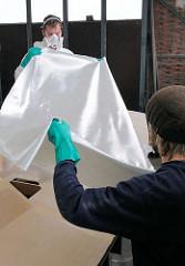 Aufnehmen der grob zugeschnittenen Glasfasermatte für die Laminierung des Decks.