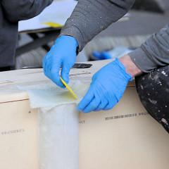 Aufbringen von Glasfasergewebe mit Epoxidharz und Spachtel.