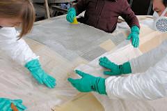 Aufbringen der Glasfasermatte auf den mit Epoxidharz eingestrichen Deckaufbau; andrücken des Gewebes vorsichtig von Hand.
