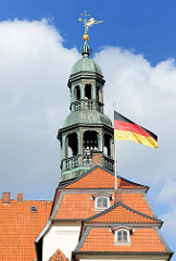 Deutschlandfahne im Wind - Dächer und Kupferturm mit goldener Wetterfahne des Lüneburger Rathauses.