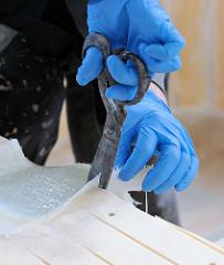 Beschneiden der aufgebrachten Glasfaser mit einer Schere.