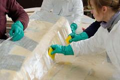 Aufbringen von Epoxidharz bei Laminierungsarbeiten.