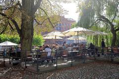 Restaurant / Café im Freien am Fischmarkt von Lüneburg - Gäste sitzen unter Sonnenschirmen an der Ilmenau.
