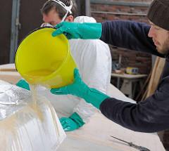 Aufbringen von Epoxidharz beim Laminieren des Decks.