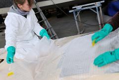 Aufbringen der Glasfasermatte auf den mit Epoxidharz eingestrichen Deckaufbau.