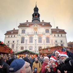 Rathaus von Lüneburg - Weihnachtsmarkt auf dem Marktplatz. Das Lüneburger Rathaus ist ein Beispiel mittelalterlicher und frühneuzeitlicher profaner Architektur in Norddeutschland. Es entstand um 1230, wurde über Jahrhunderte hinweg immer wieder erwei