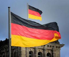 Flagge der Bundesrepublik Deutschland / Bundesflagge - deutsches Hoheitszeichen / Staatssymbol; wehen im Wind beim Reichstagsgebäude in Berlin.