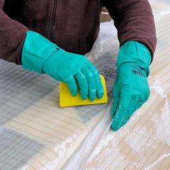 Andrücken der Glasfasermatte mit einem Spachtel in das Epoxidharz.