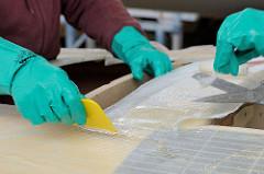 Verspachteln von Epoxidharz - Beschneiden von überstehender Glasfasermatte mit der Schere.