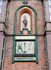 Skulptur und Lüneburgwappen an der Fassade vom 1905 erbauten Gebäude des Graalstift.