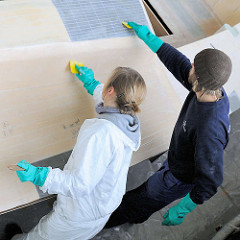 Laminieren vom Bootsdeck des Daysailors Lütje 35 - auftragen des Epoxidharzes mit Spachteln.
