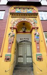 Farbenfroher Eingang der Alten Ratsapotheke in Lüneburg; erbaut um 1500. Halbplastisches Renaissanceportal - zwei Figuren tragen Apothekengefässe.