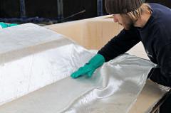 Laminieren des Deckaufbaus vom Daysailor Lütje 35 - die Glasfasermatte wird von Hand an das vorher aufgebrachte Epoxidharz gedrückt.