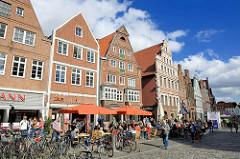 Häuser am historischen Lüneburger Platz Am Sande, Giebelhäuser - Cafés auf der Strasse in der Sonne; blauer Himmel - weisse Wolken.