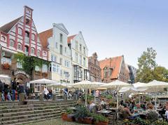 Aussengastronomie am Stintmarkt an der Ilmenau in der Hansestadt Lüneburg. Gäste sitzen unter Sonnenschirmen an der Ilmenau.