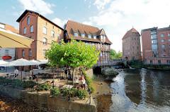 Restaurant / Café im Freien am Fischmarkt von Lüneburg - Gäste sitzen unter Sonnenschirmen an der Ilmenau. Im Hintergrund das Gebäude der Lüner Mühle / Alte Ratsmühle aus dem Jahr 1597; Ilmenau Hafen.