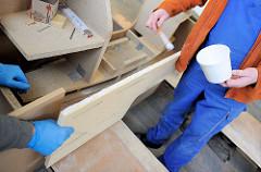 Fertigung des Deckaufbaus - Bestreichen eines  Bauteils mit Leim.