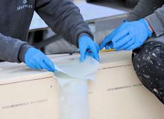 Anbringen von Glasfasergewebe mit Epoxitharz - Handarbeit beim Bau des Daysailers Lütje 35 in der Hansestadt Hamburg.