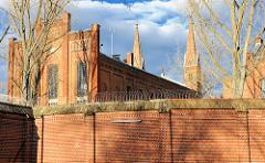 Gefängnismauer mit Stacheldraht - Anstaltskirche des zwischen 1868 und 1879 Strafgefängnis Plötzensee in Berlin .