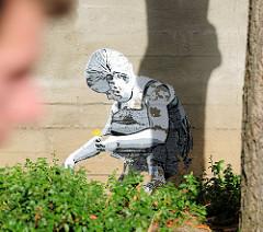 Graffiti an einer Hauswand in Lüneburg - ein Kind / kleines Mädchen sitzt im Gras + pflückt Blumen - es wird von einem Mann beobachtet.