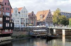 Aussengastronomie am Stintmarkt an der Ilmenau in der Hansestadt Lüneburg - zwei historische Boote, darunter ein sogenannter Salzewer liegen im Hafenbereich.