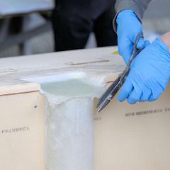 Zuschneiden des mit Epoxidharz aufgebrachten Gewebes mit einer Schere - die Hände sind mit Arbeitshandschuhen / Gummihandschuhen geschützt.