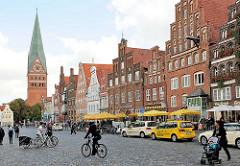 Platz Am Sande in Lüneburg - Fussgänger, Fahrradfahrer, Taxis warten am Taxistand - historische Architektur / Kirchturm der St. Johanniskirche.