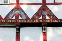 Kunstvoll verzierte, geschnitze Dekor-Fachwerkbalken mit goldener Inschrift - Fachwerkhaus am Lüneburger Kloster.