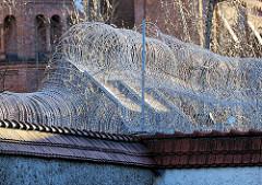 Gefängnismauer mit Stacheldraht des zwichen  1868 und 1879 errichteten Strafgefängnis Plötzensee in Berlin.