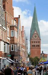 Geschäftshäuser, Passanten auf dem Platz Am Sande in Lüneburg, Kirchturm der St. Johanniskirche.