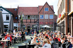Strassencafe / Tische mit Gästen in der Sonne - Schrangenplatz / Schröderstrasse in der Hansestadt Lüneburg.
