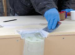 Spachteln von Übergängen mit Epoxidharz am Deck des Seglers.